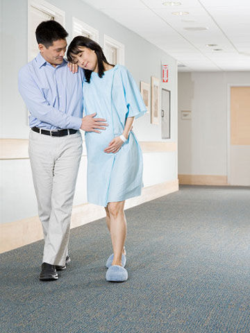 pregnant woman walking in hospital with husband