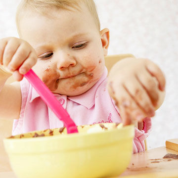baby eating pudding and making mess