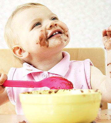 baby in highchair eating pudding