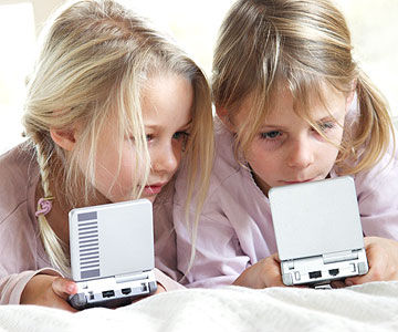two girls playing handheld video games