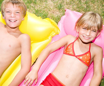 young boy and girl in bathsuits on rafts