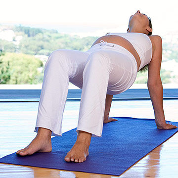 pregnant woman stretching on yoga mat