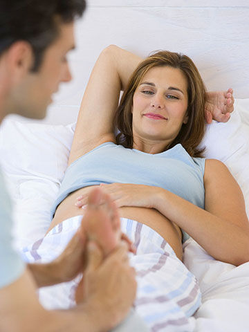 man giving pregnant wife foot massage