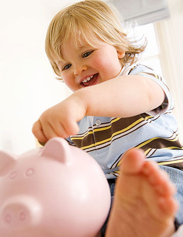 toddler putting money in piggy bank