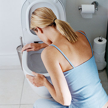 woman getting sick into the toilet