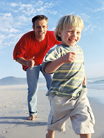 Dad chasing blond son on sand near ocean