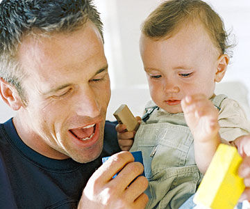 Dad playing and showing objects to baby girl