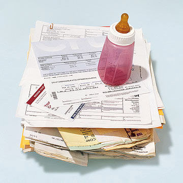 Pile of Bills with Pink Baby Bottle on Top