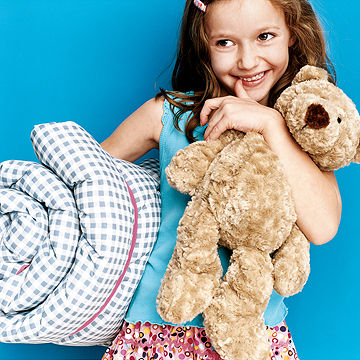 girl holding her bear and sleeping bag