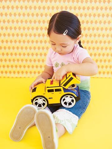 Girl Playing with Toy Truck
