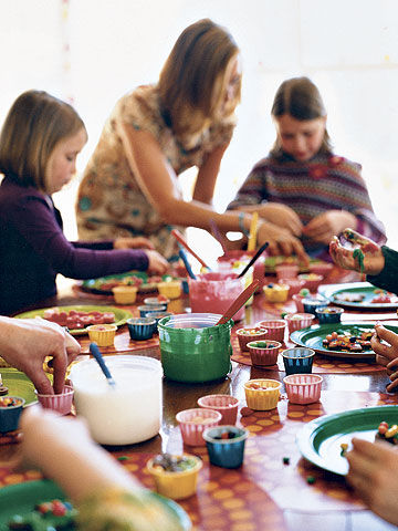kids around table decorating cookies