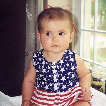 Little Girl In Stars and Stripes Outfit Sitting In Front Of Window