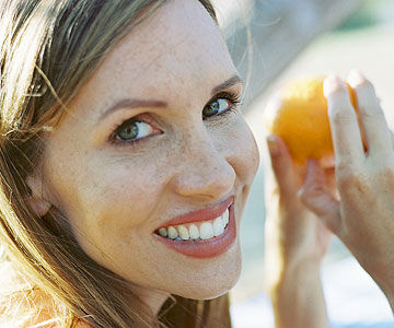 woman smiling holding fruit