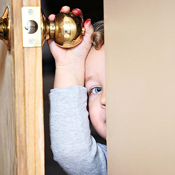 toddler hiding behind door