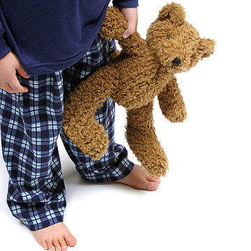 child in pajamas holding teddy