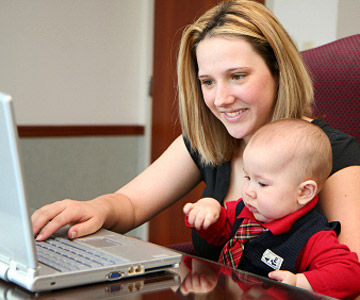 mom on computer holding baby in lap