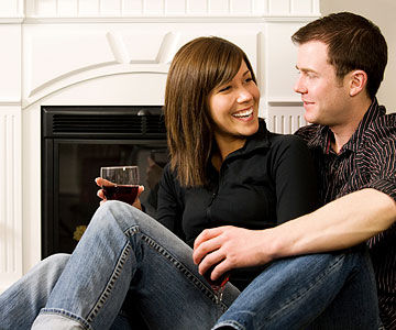 couple talking and drinking red wine by fireplace