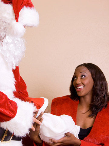 mother holding baby out to Santa Claus