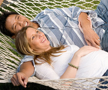 pregnant woman lying in hammock with husband