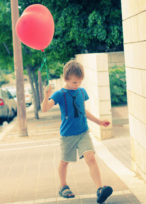 Autistic boy holding a red balloon