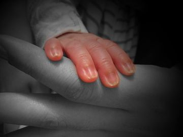 baby hand in color on black and white