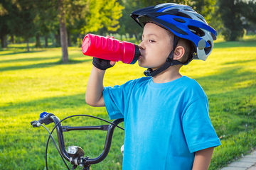 boy drinking from water bottle after biking
