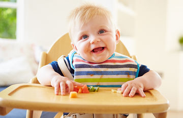 child in high chair eating fruit
