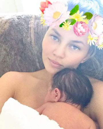 Chrissy Teigen Snap with Coachella filter and flower crown holding baby Luna.