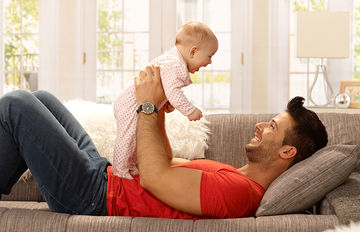 dad playing with baby at home