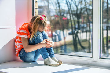 little girl crying on a window sill
