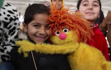 refugee girl hugging muppet