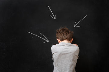 Sad boy standing at a blackboard with arrows