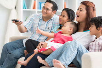 asian family watching tv together at home