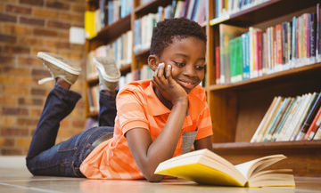 happy boy reading in library