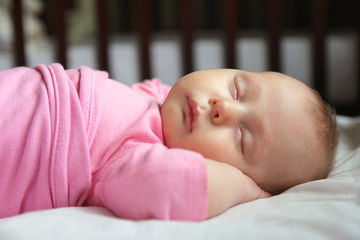 baby sleeping in pink swaddle