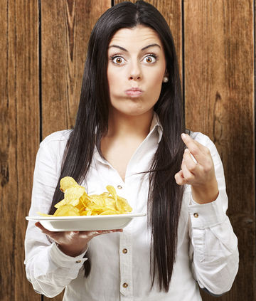 surprised woman eating plate of potato chips