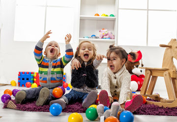 three young children playing with colorful balls