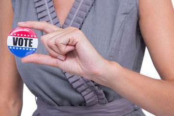 woman holding vote button
