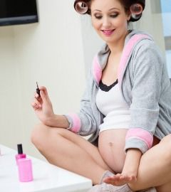 pregnant woman painting nails pink