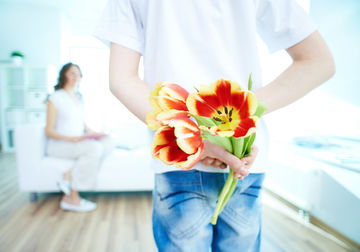 Child holding flowers for mom
