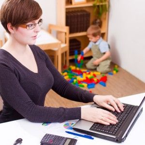 Woman Typing on Laptop with Child Playing in Background