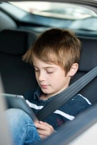 boy playing with tablet in car
