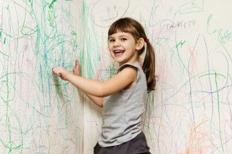 Girl coloring with crayon on walls