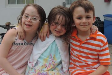 Three happy kids on vacation, including our daughter with Down syndrome