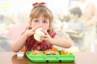 Girl eats school lunch in cafeteria