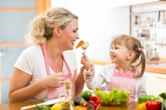 Mother and daughter eating fresh vegetables