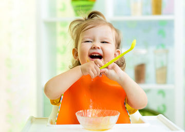 laughing baby eating with spoon