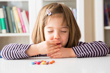 little girl eating chocolate candies
