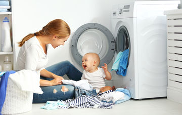 Mother and Baby Do Laundry Laughing