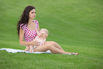 mom breastfeeding in meadow